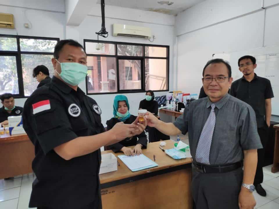 Rektor Unisma Bekasi, Dr. Nandang Najmulmunir, Ir., M.S, menyerahkan urine kepada petugas